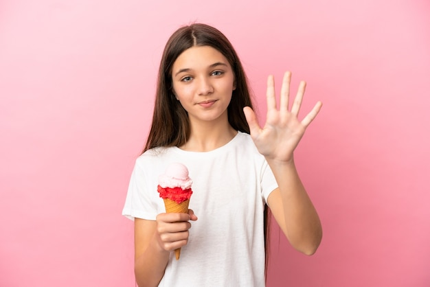 Маленькая девочка с мороженым корнет на изолированном розовом фоне, считая пять пальцами