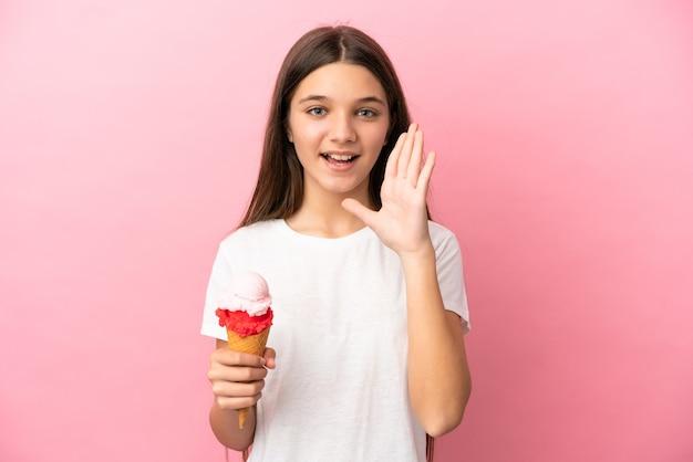 Маленькая девочка с мороженым корнетом на изолированном розовом фоне кричит с широко открытым ртом