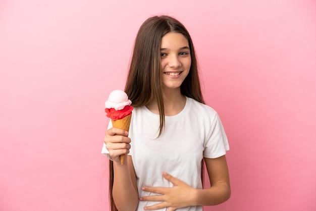 고립된 분홍색 배경 위에 코넷 아이스크림을 들고 많이 웃고 있는 어린 소녀