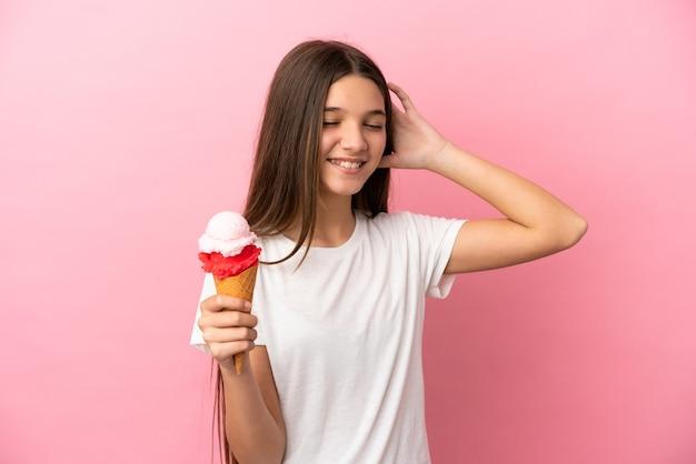 Маленькая девочка с мороженым корнет на изолированном розовом фоне много улыбается