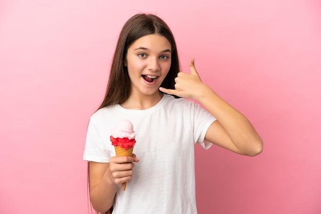 電話のジェスチャーを作る孤立したピンクの壁の上にコルネットアイスクリームを持つ少女