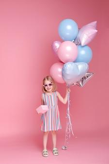 분홍색 표면에 선물 및 풍선 어린 소녀