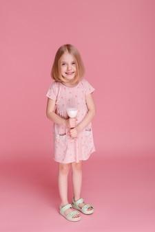분홍색 표면에 우유 한 잔과 어린 소녀