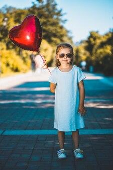自然の中でハート型の風船を持つ少女