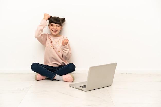 승리를 축하하는 바닥에 앉아 노트북으로 어린 소녀