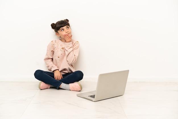 Маленькая девочка с ноутбуком сидит на полу, глядя вверх, улыбаясь