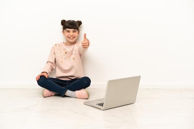 Маленькая девочка с ноутбуком сидит на полу с большими пальцами руки вверх, потому что произошло что-то хорошее