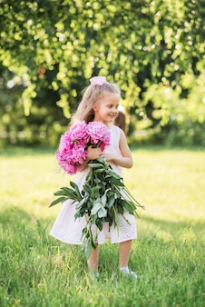 牡丹の大きな花束を持つ少女。夏には子供が花を持って公園を散歩します。