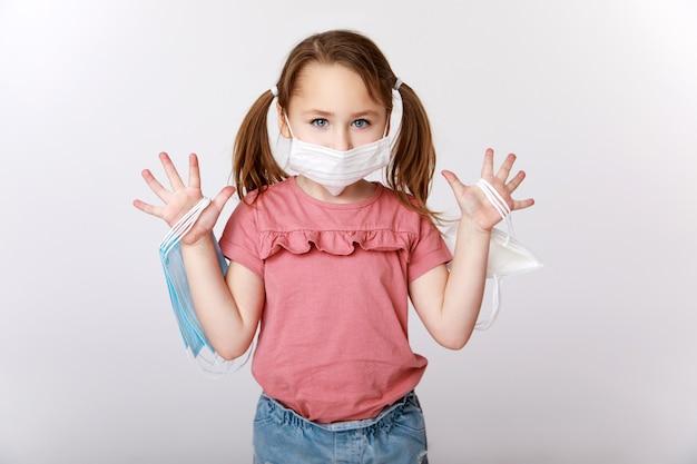 Маленькая девочка с медицинской маской на лице, держащая множество медицинских масок и масок ffp2 Premium Фотографии
