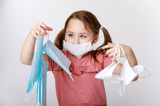 Маленькая девочка с медицинской маской на лице, держащая множество медицинских масок и масок ffp2
