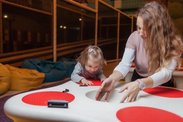 유모가있는 어린 소녀가 어린이 엔터테인먼트 센터의 테이블에서 장난감 벽돌을 연주합니다.