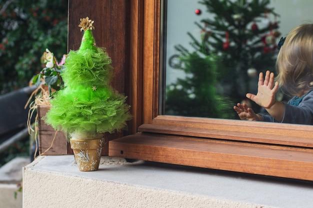 クリスマスツリーを見ているガラスの上の手のひらを持つ少女