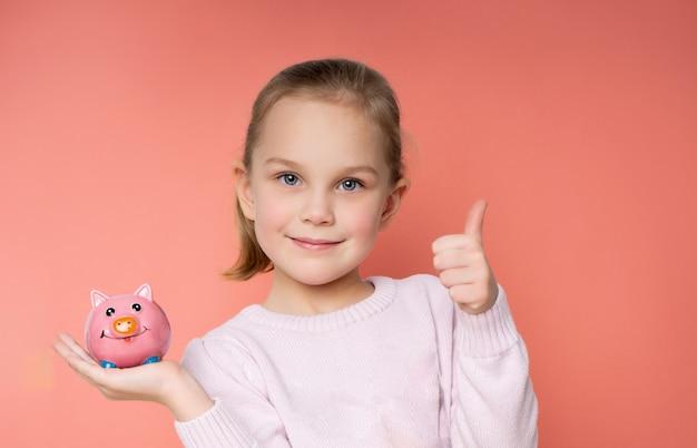 Маленькая девочка с копилкой в руках показывает класс