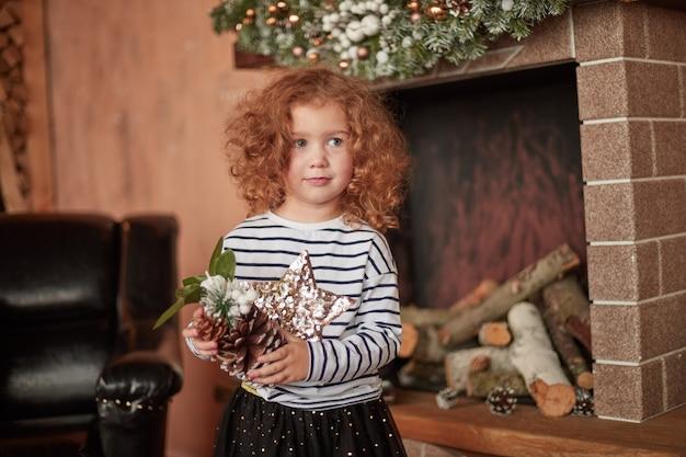 크리스마스 이브에 벽난로 옆 소나무 콘 서있는 어린 소녀.