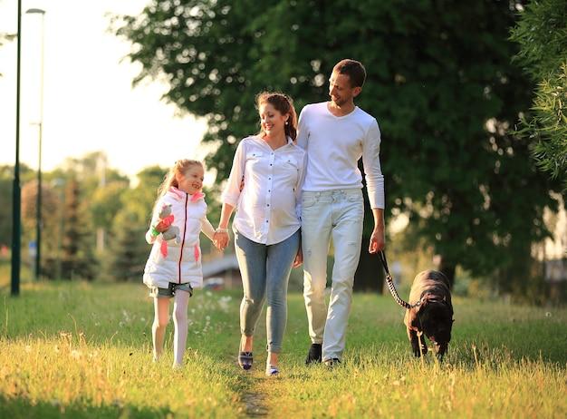 Маленькая девочка с беременной матерью, счастливым отцом и собакой на прогулке в парке в весенний день