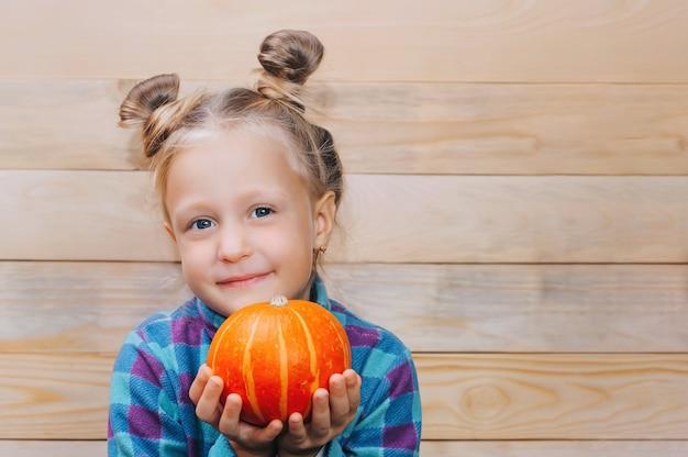 Маленькая девочка с тыквой в руках на фоне деревянных досок.