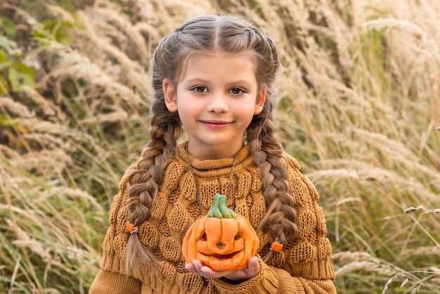 Маленькая девочка с тыквой в руках.