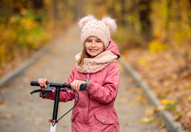 秋の公園の道路に立って笑っているスクーターを持つ少女