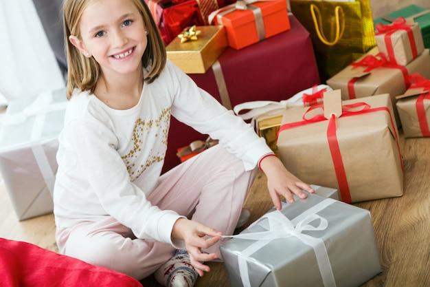 Маленькая девочка с подарок серебряный улыбается