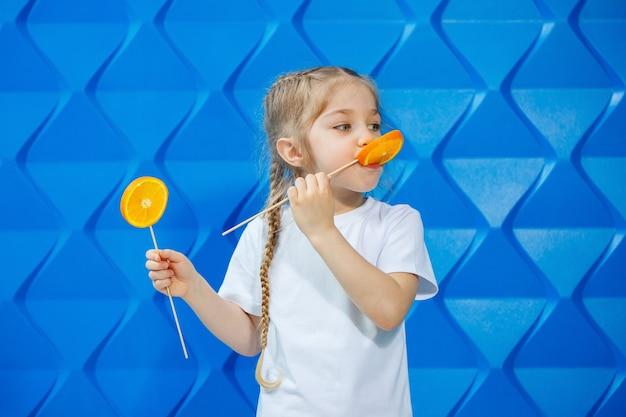 하얀 티셔츠를 입은 미소와 땋은 머리를 한 어린 소녀는 건강한 생활 방식의 개념인 오렌지 반을 손에 들고 있습니다.