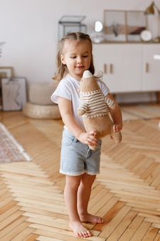 집의 거실에서 부드러운 장난감을 가진 어린 소녀