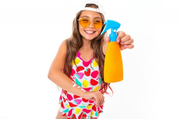 Маленькая девочка со спреем для защиты кожи от ультрафиолетовых лучей на белом фоне