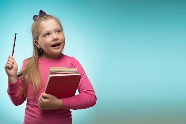 Маленькая девочка с стопку книг и карандаш в ее руках на синем фоне. обратно в школу и концепции образования.