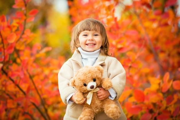 Маленькая девочка с плюшевым мишкой в руке на фоне осенней листвы. осенняя пора.