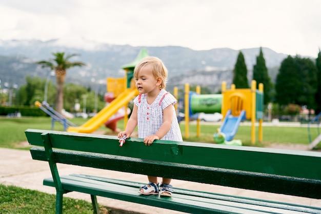 장난감을 손에 들고 있는 어린 소녀는 놀이터의 벤치에 서 있다