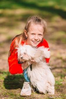 Маленькая девочка с белым щенком. щенок на руках у девочки