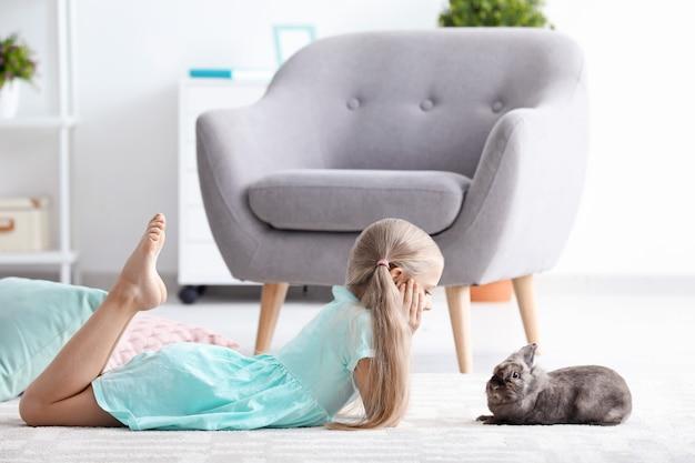 Маленькая девочка с очаровательным кроликом в помещении