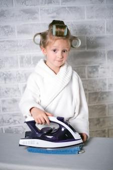 アイロンをかけられる洗濯物の量を持つ少女、彼女の頭にカーラーが付いている白いコート