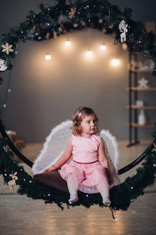 Little girl with angel wings sitting on fir wreath.