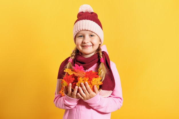 Little girl with an armful of autumn maple leaves.