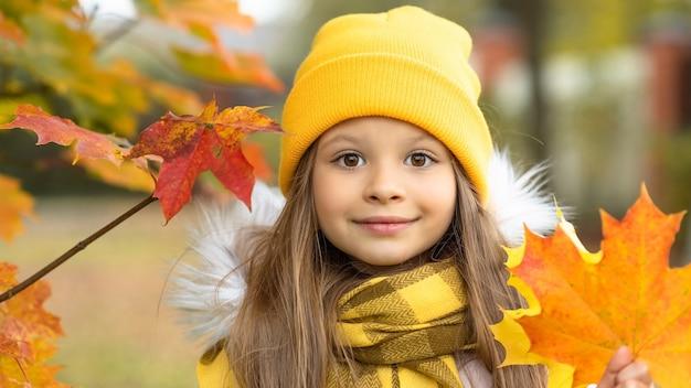 秋の黄色のカエデの葉を持つ少女。