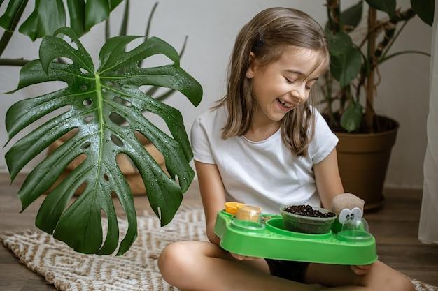 Una bambina con un kit per bambini per far crescere una pianta da sola.