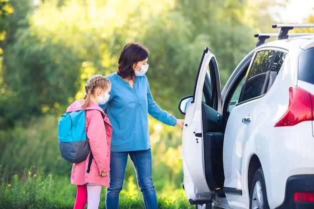 バックパックを背負った少女と医療用マスクを着用した母親が車で学校に到着