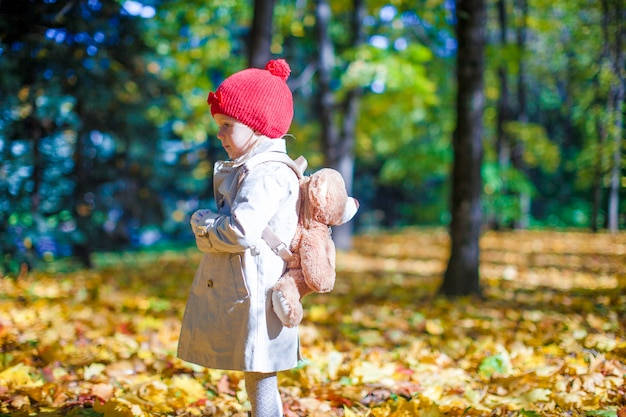 Little girl with a backpack-bear walks in the autumn forest on beautiful sunny day