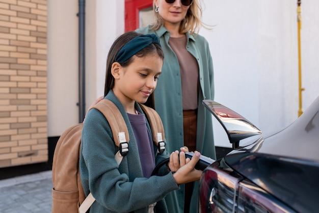 Маленькая девочка с рюкзаком помогает матери заряжать автомобильный аккумулятор ev