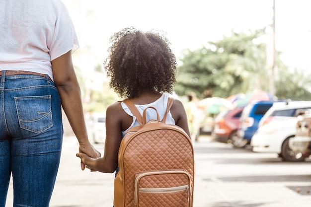 배낭을 메고 있는 어린 소녀가 사람의 손을 잡고 있습니다. 학교 개념으로 돌아가기.