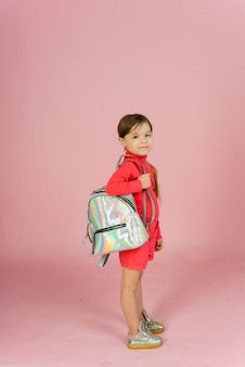 Little girl with a backpack on a pastel pink background