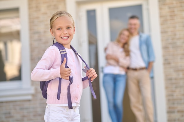 Little girl with backpack showing ok and parents