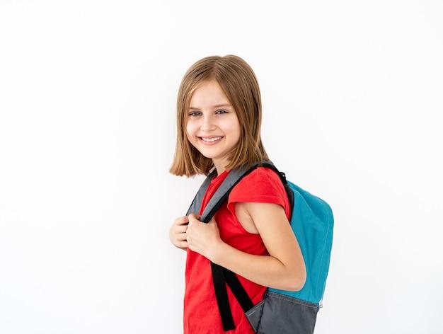 白で隔離横に立っているバックパックを持つ少女