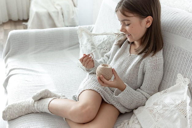Little girl with a ball of thread and a needle at home on the couch.