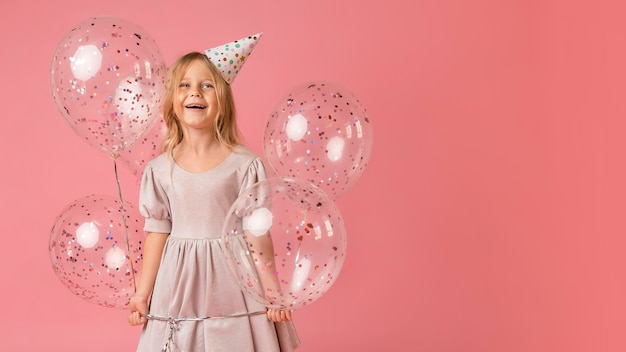 Little girl with balloons in costume and copy space