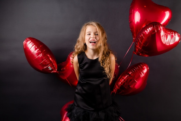 A little girl with balloons in the form of a heart send a kiss on a black background