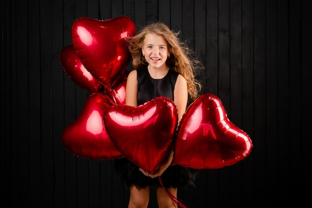 A little girl with balloons in the form of a heart send a kiss on a black background.