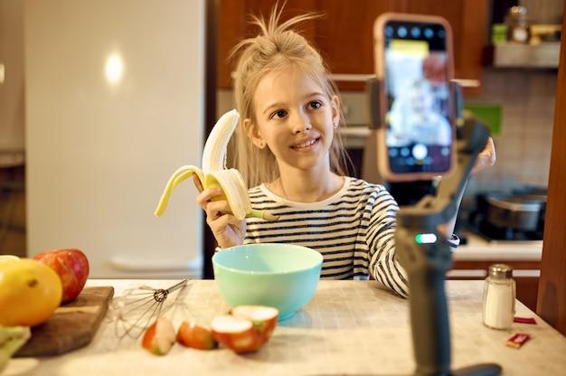 Маленькая девочка с бананом делает блог о еде, детский блогер. детские блоги в домашней студии, соцсети для юной аудитории, онлайн-трансляции, творческое хобби