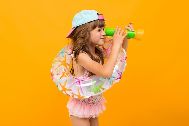 Little girl with a baseball cap in a swimsuit with a swimming circle on a yellow wall