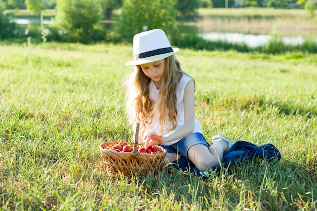 Little girl with basket strawberries